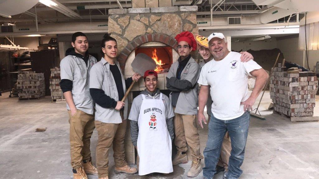 Class of 2018 students stand before their newly completed Bread Oven (pizza!!) project.
